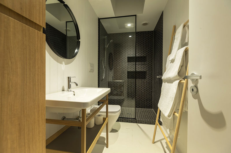 Dark hexagonal tiles fill the shower in this modern bathroom, while a black framed glass shower partition separates the shower from the vanity, that has white tiles and light wood elements.