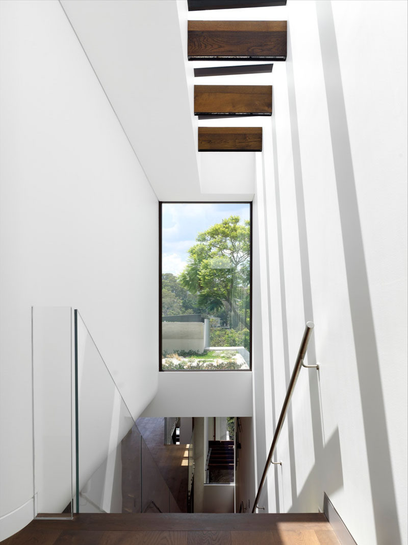 Stairs with a glass handrail and skylight above lead to the next lower level of this house, while a large window provides a glimpse of the green roof outside.