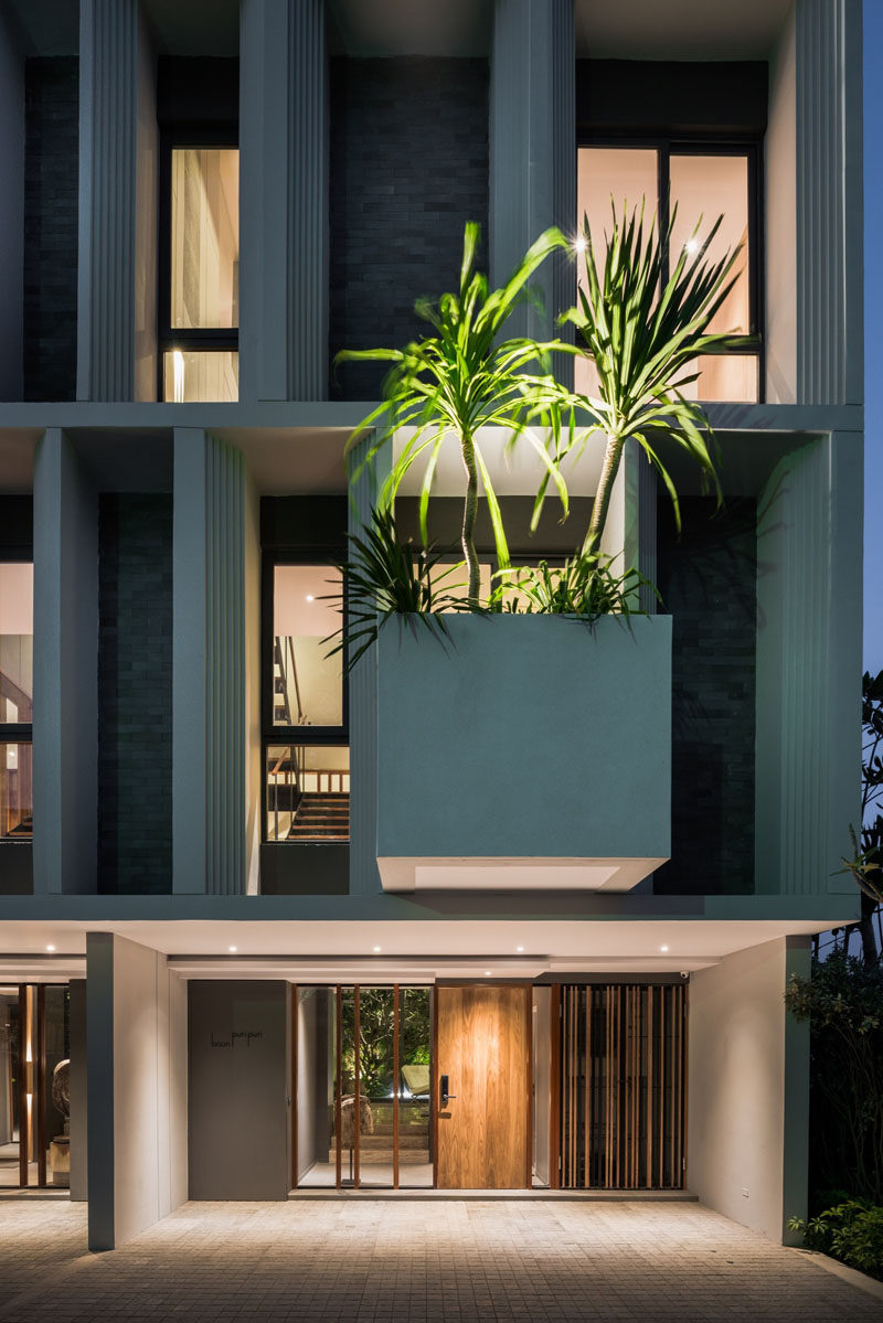 This modern townhouse has a large cantilevered planter box that stands out and add a touch of nature to the facade.