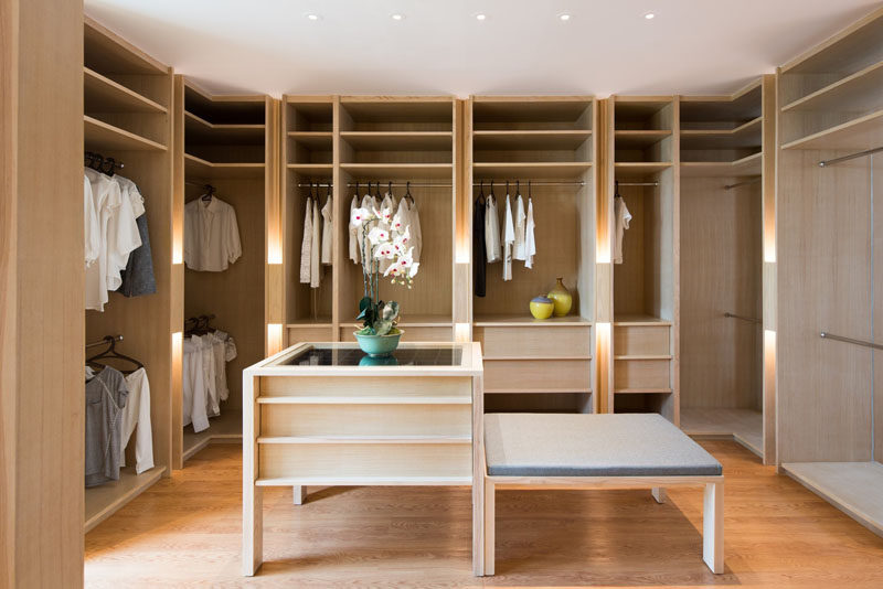 This large walk-in closet has plenty of light wood open shelving as well as drawers for storage. In the center of the closet is an accessories island and an upholstered bench.