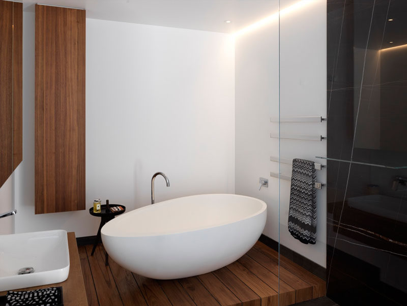 In this modern master bathroom, bright white walls have been combined with wooden elements, while a white standalone bathtub is the focal point.