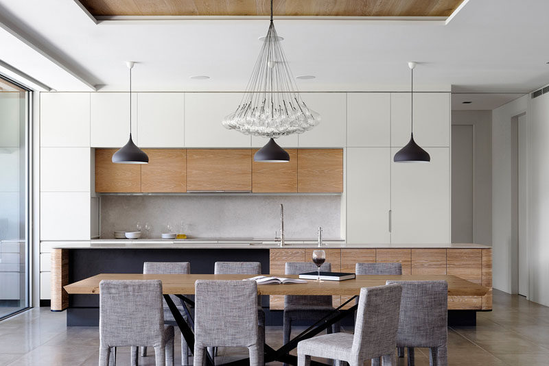This modern kitchen features a stone countertop, solid timber doors and over-sized ceramic floor tiles. The dining room is made up of a large wood table, upholstered dining chairs and a large pendant lamp hanging above.