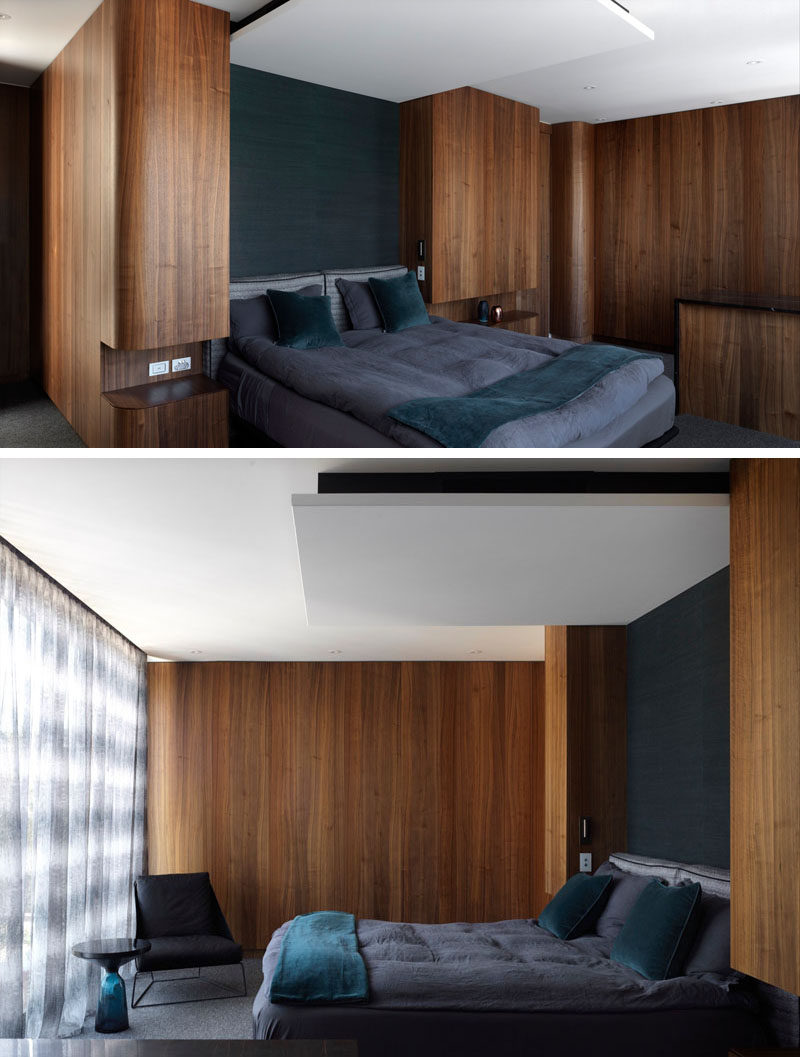 This modern bedroom features rich wood walls and built-in bedside tables, and when combined with grey bedding gives off a luxurious feeling.