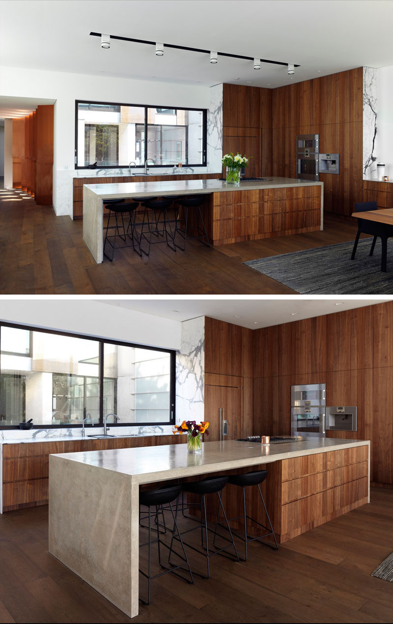 In this kitchen, dark wood cabinets have been combined with a light stone countertop to create a contemporary appearance. Large windows above the kitchen sink provide views of the courtyard.