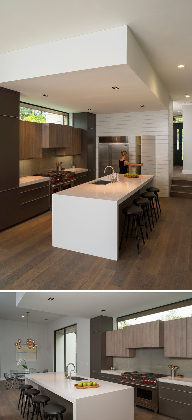 In this modern kitchen, the large white island with seating has plenty of room for guests to sit and chat, and a hidden pantry sits beside the fridge.