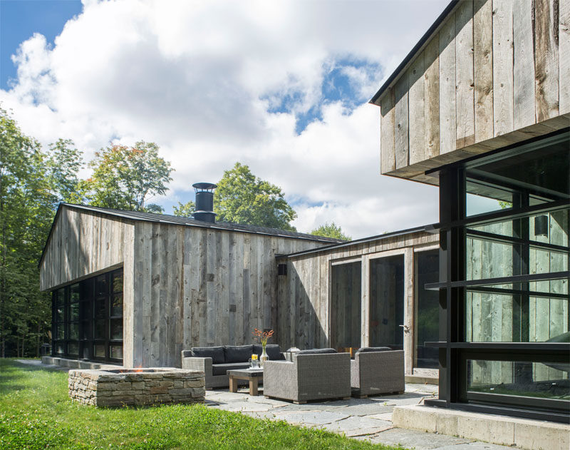 Opposite the entryway in this modern wood house is a door that leads out to an outdoor entertaining space with a couch, a couple of armchairs and an outdoor firepit.