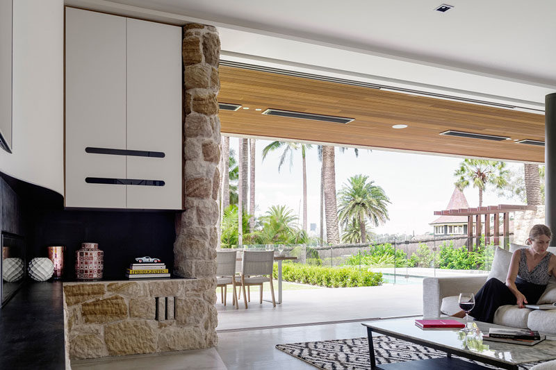 Floor-to-ceiling windows separate the outdoor space from the interiors of this modern house. When opened, the large over-sized windows are concealed within the wall behind the stonework and cabinetry.