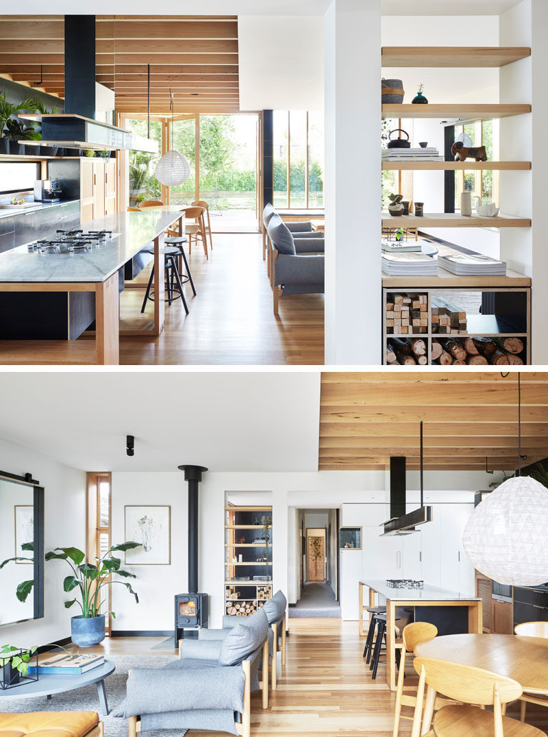 This modern wood house extension is an open room with the kitchen, dining and living room all sharing the same space. White walls have been combined with wood to create a sense of warmth, and large folding doors open to the backyard.