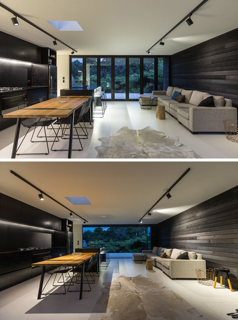Inside this modern house, the living, dining and kitchen share the same room. The dark wood exterior siding continues through to the interior behind the couch, and compliments the black kitchen on the opposite wall.