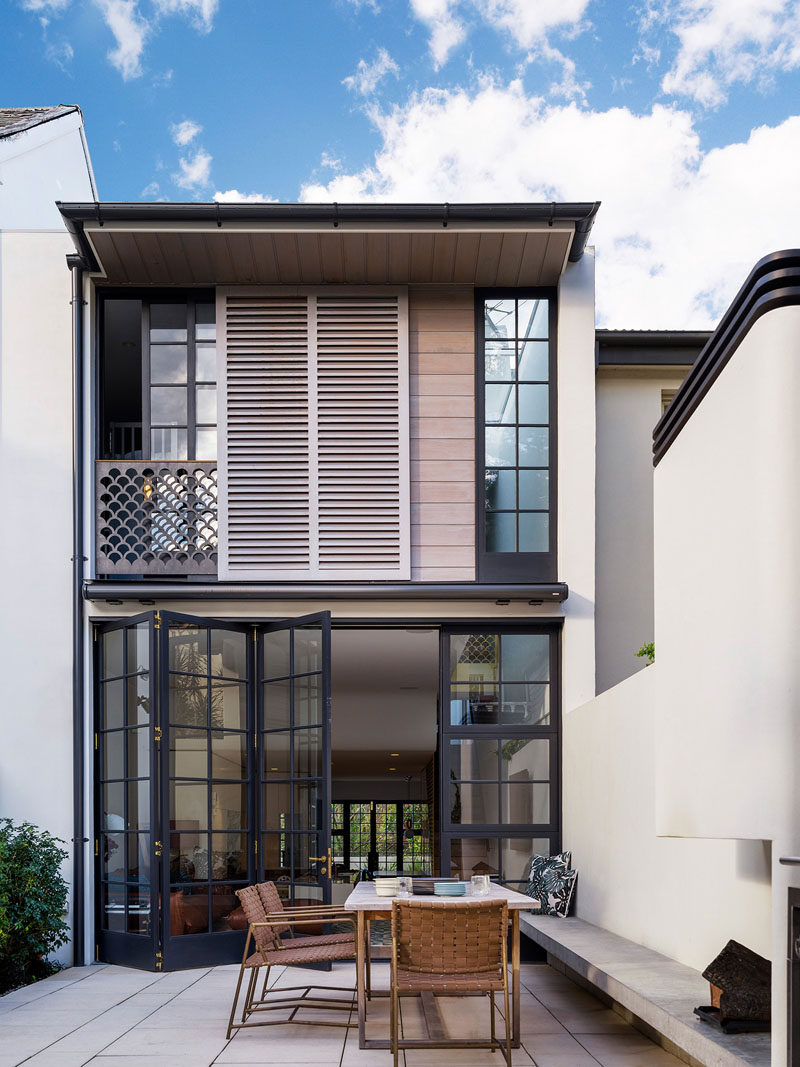 This modern row house has an internal courtyard at the rear of the home accessed through the main floor. A built-in bench provides seating for an outdoor dining table.