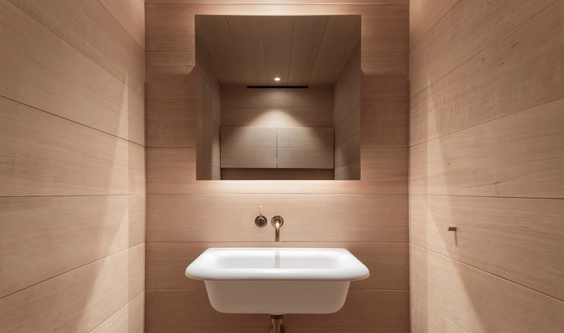 This small bathroom has wood covered walls, a backlit mirror and a simple white sink.