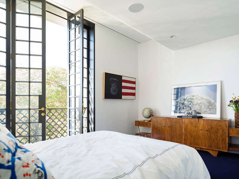 On the second floor of this modern house is a bedroom with tall French doors that open inwards, allowing for fresh air and plenty of light to fill the room.