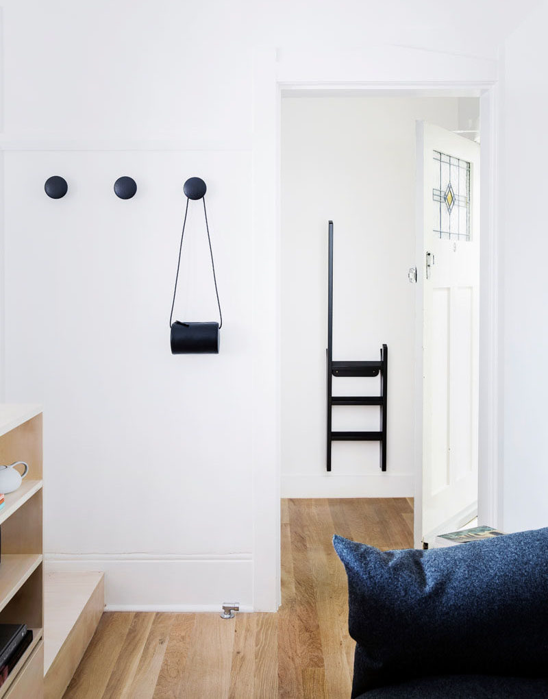 Simple round matte black hooks match the step ladder that hangs behind the front door in this small apartment.