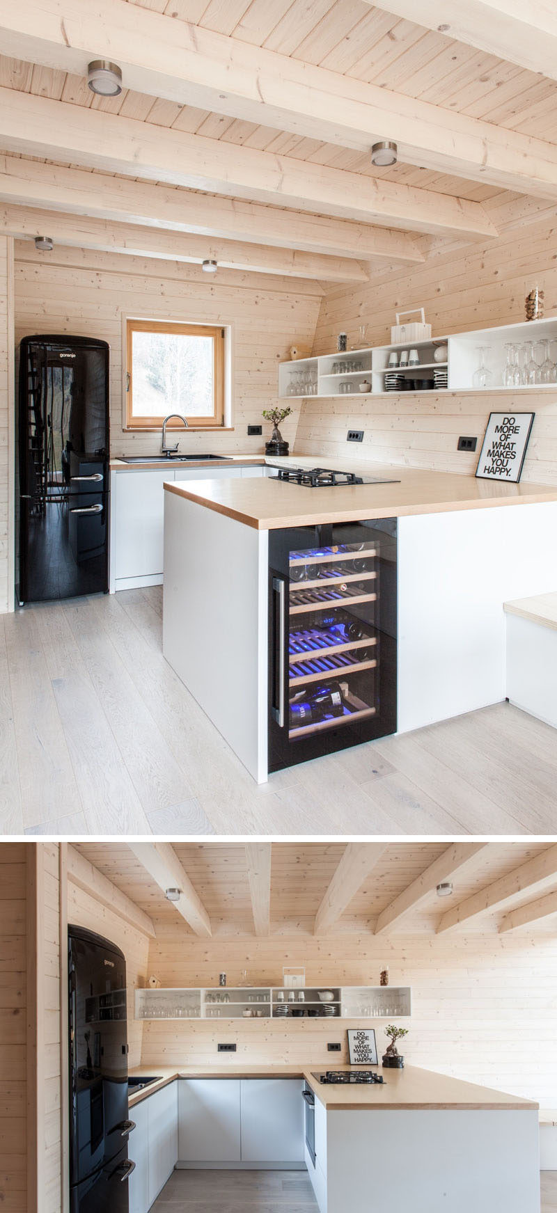 This light wood kitchen has a u-shaped layout with white hard-ware free cabinets, a wood countertop and open shelves that float on the wall. Black elements, like the fridges and sink and artwork, are also featured.