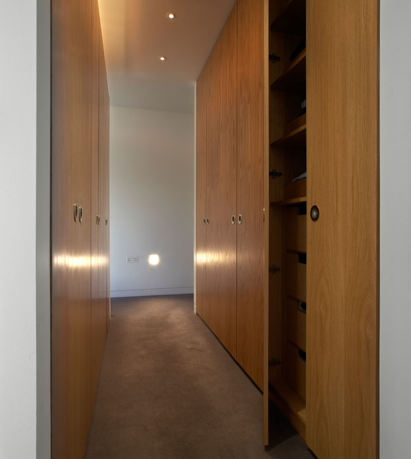 This modern walk-in closet has tall wood cabinets and plenty of storage.