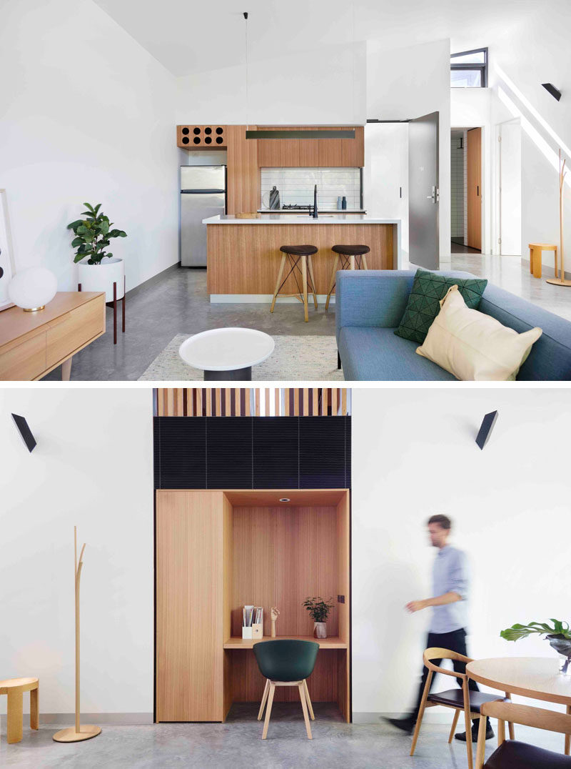 This modern apartment has a light wood and white kitchen, white a small study nook has been built into the wall and uses the same wood as the kitchen.