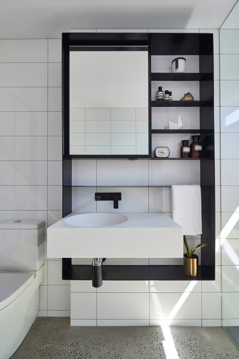 This modern bathroom has white tiles that have been paired with a black wall cabinet for a bold and contrasting look.