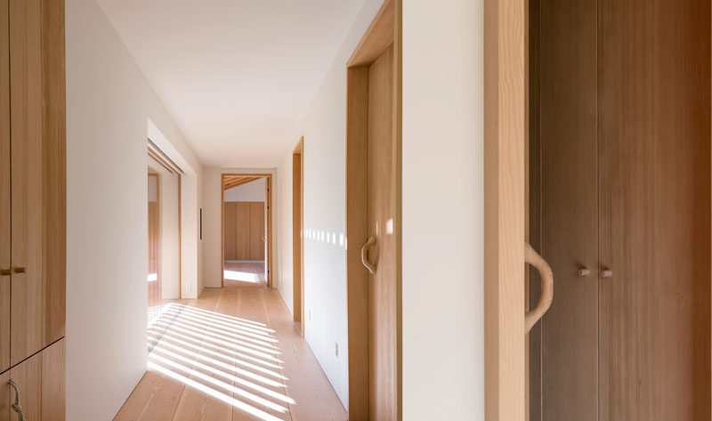 White plaster covers the walls in this hallway, and when paired with light wood doors and flooring, creates a contemporary interior.