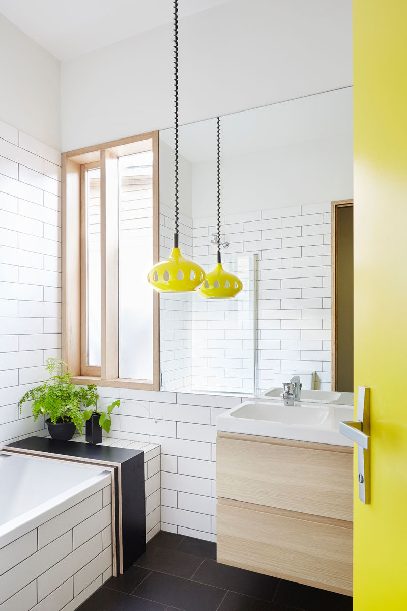This modern bathroom has a bright yellow door that matches a fun pendant light of the same color, while the remainder of the bathroom is black and white.