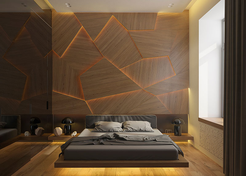 A modern bedroom with a geometric wood panel accent wall and hidden LED lighting.