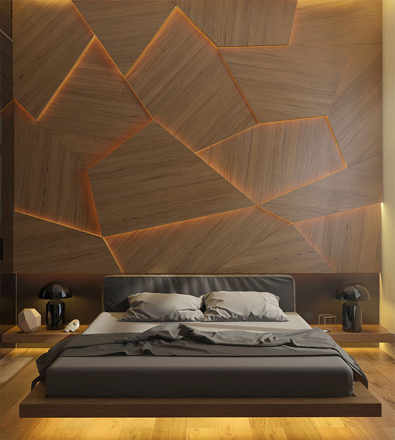 This bedroom has a geometric back lit wood accent wall for Wooden hotel design