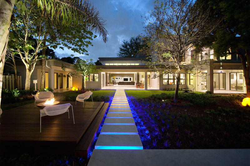 This modern path is lit by LED lights, leading from the patio to an entertaining space with seating and a firepit.