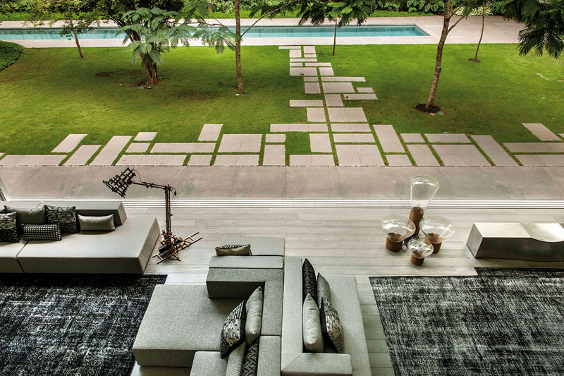 Square concrete pavers are arranged geometrically in the backyard of this modern home creates a distinctive walkway.