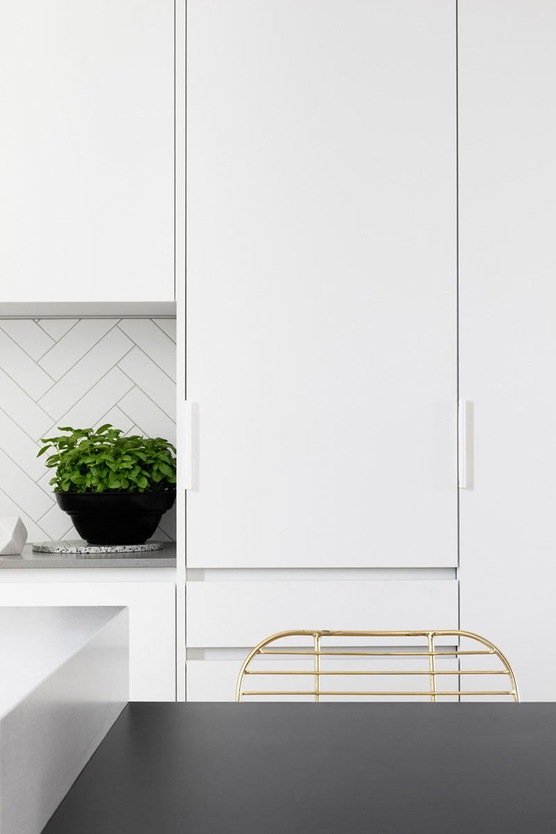 These white kitchen cabinets have minimalist white hardware that almost blends in with the cabinetry, helping to create a streamlined look.