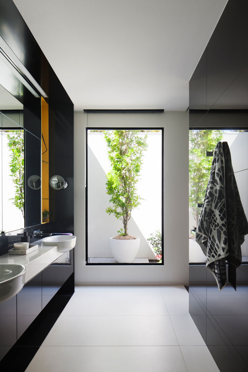 In this modern master bathroom, a tall window perfectly frames a potted plant outside, while a dual sink vanity with black cabinetry and a white counter makes sure there's plenty of room for personal items. There's also a toilet and a walk-in shower.