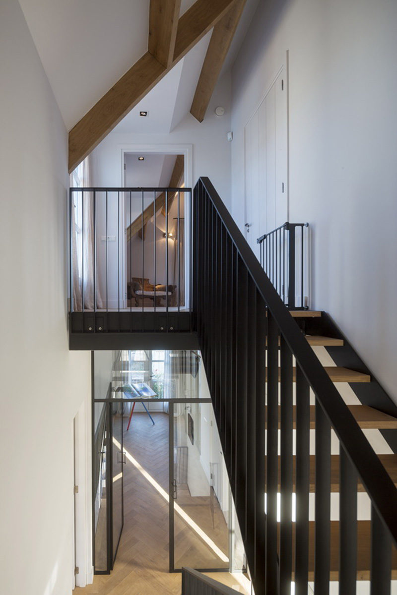 Wood and black steel stairs lead up to the top floor of this modern home.