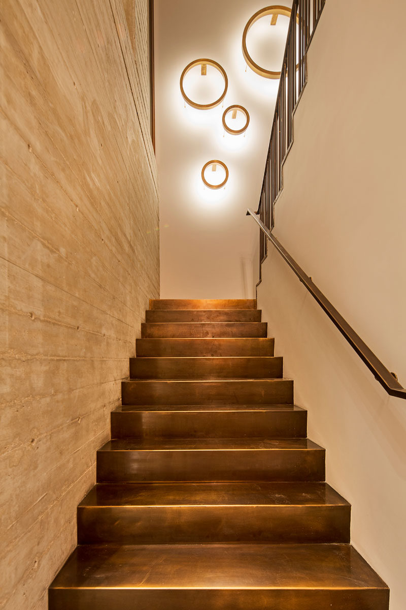 In this modern house, a staircase with bronze stairs and a concrete wall leads you up to the second floor of the home.