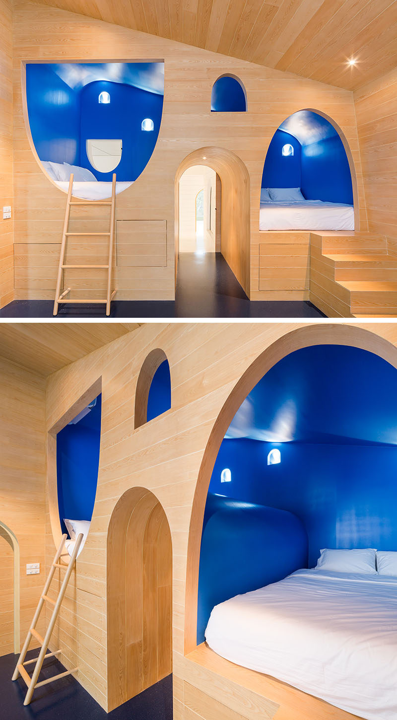 This whimsical yet modern boys bedroom features two built-in beds surrounded by royal blue walls that are built into the light wood wall.