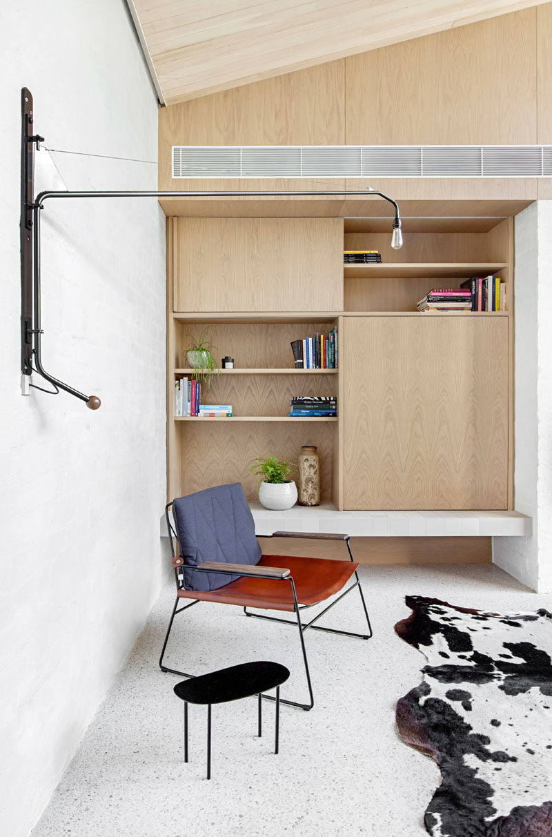 This modern living room has a built-in wood bookshelf with open shelving. A movable metal wall light adds an industrial touch to the room.