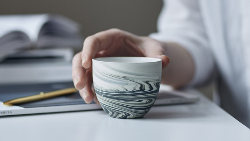 This modern ceramic espresso cup has a matte grey black swirl pattern.