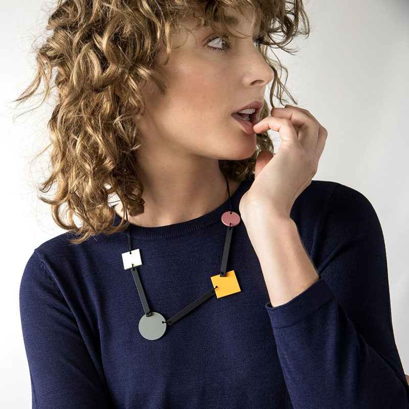 Colored circles and squares connected by black rectangles, give this necklace a distinctive geometric look that's both simple and artistic.