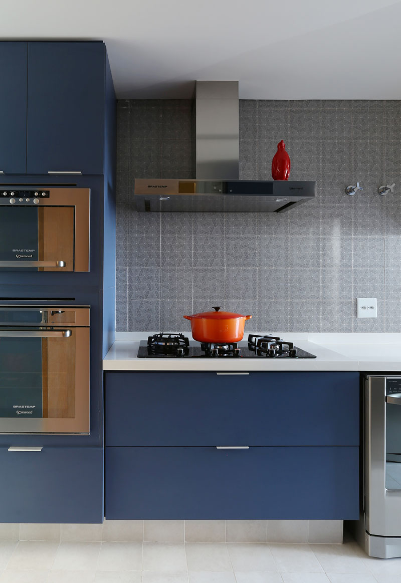 The deep periwinkle matte blue on the cabinets of this modern kitchen warm it up and soften up the stainless steel appliances.