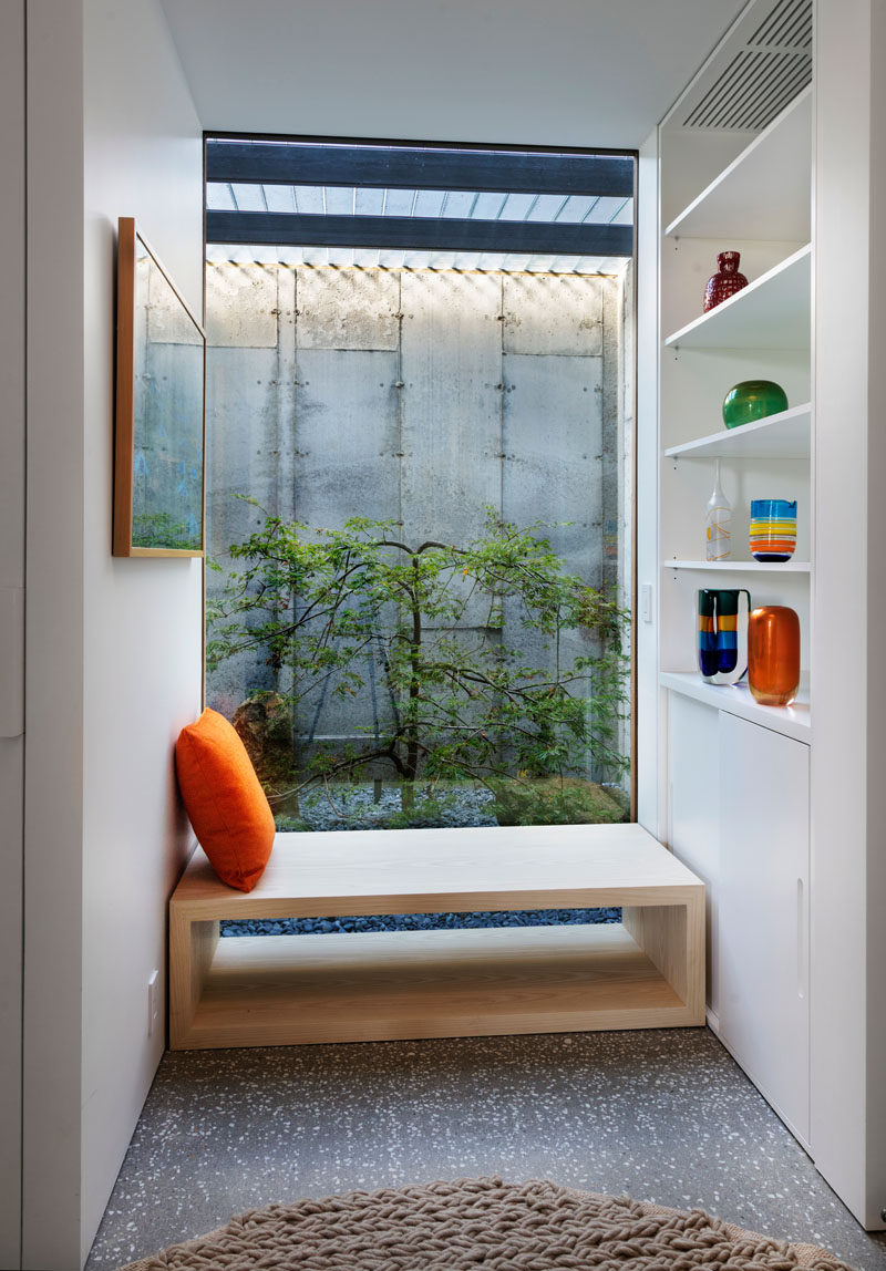 This modern house has a small nook with wood bench seating, a large window and built-in white shelving and storage.
