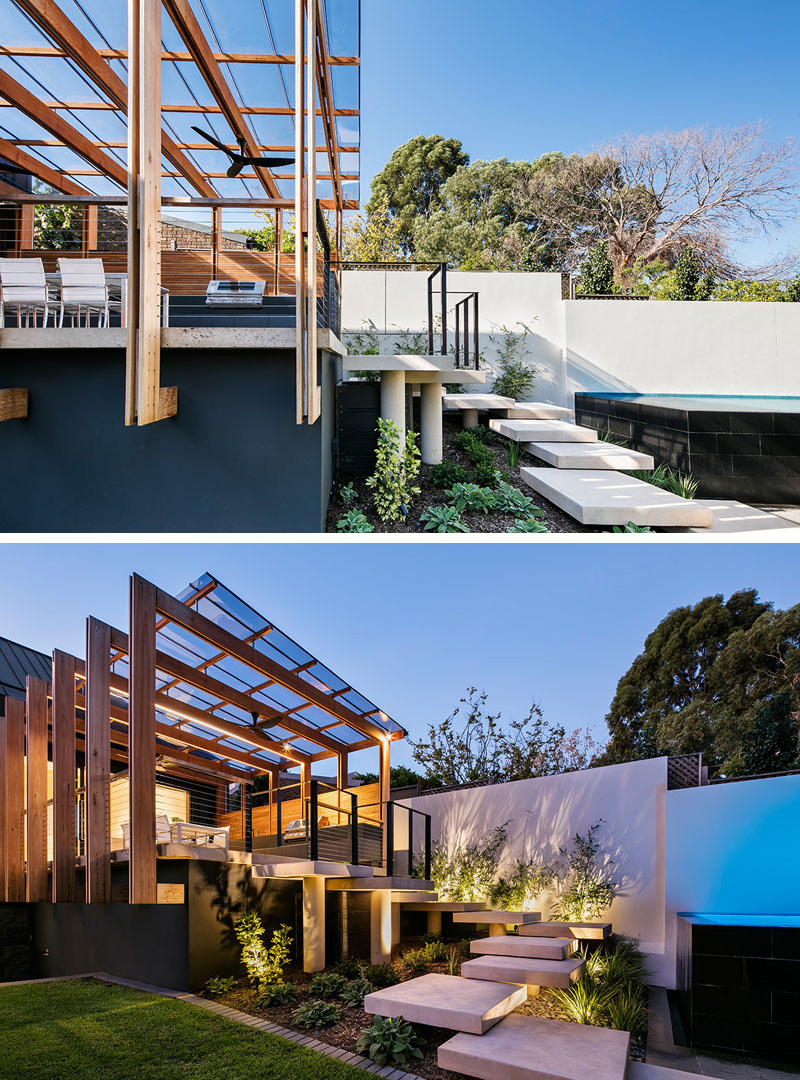 Oversized concrete steps take you from this modern entertaining deck with pergola down to the rest of the yard and lead to the above ground pool. Uplighting in the garden around the steps illuminates the path and makes it easy to see where you're going.