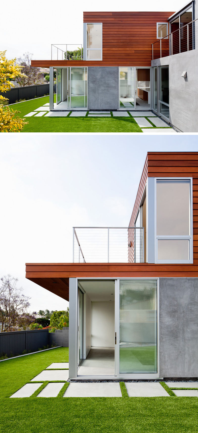 Concrete pavers go around the back of this modern house, connecting the various spaces and creating a manicured landscape.