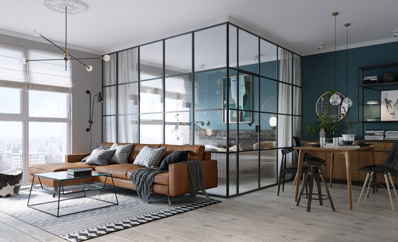 This small and modern apartment features bedroom in a black framed glass box with a deep teal accent wall.