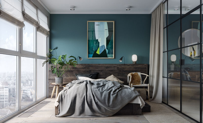 In this modern bedroom, a deep teal and wood accent wall provides the perfect backdrop for the artwork and bed, while black framed glass walls separate the bedroom from the living and dining area and allow the light from the windows to travel throughout the small apartment. At night, blinds and curtains can be drawn to provide privacy.