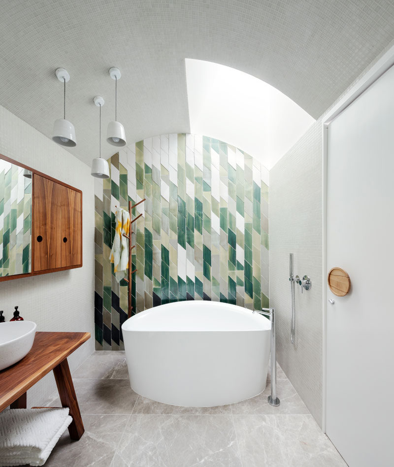Patterned tiles in shades of green, creates an accent wall behind the bath in this modern bathroom, while a wood wall cabinet and vanity tie in with the oversized circular wood door handle.