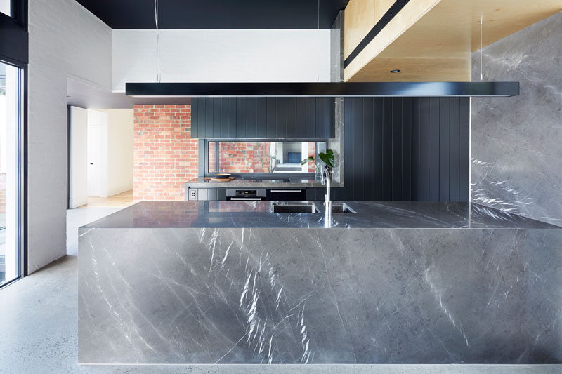 This modern kitchen has a color palette of grey and black, with a long horizontal lamp hanging above one side of the kitchen.