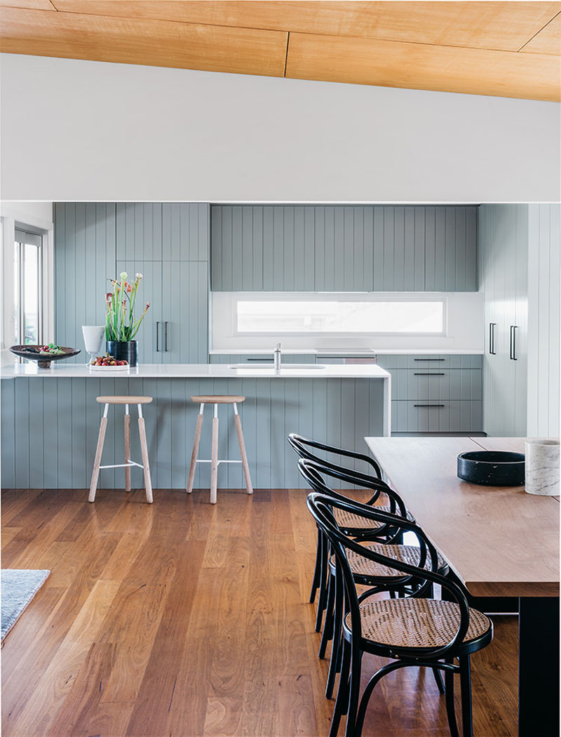 The soft blue cabinetry in this modern kitchen has been paired with bright white walls and countertops which are a strong contrast to the wood flooring.