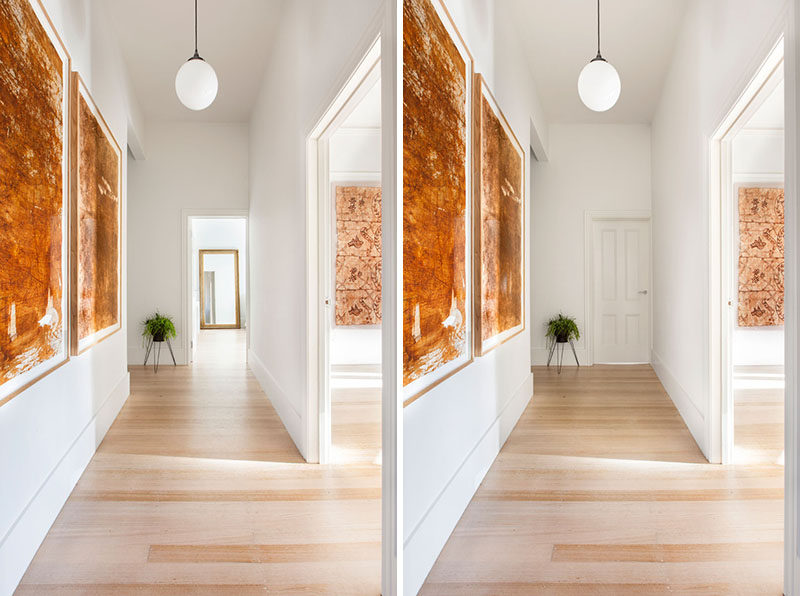 In this contemporary hallway leading to the bedrooms, light wood floors have been paired with white walls, while art and a single plant add touch of color.