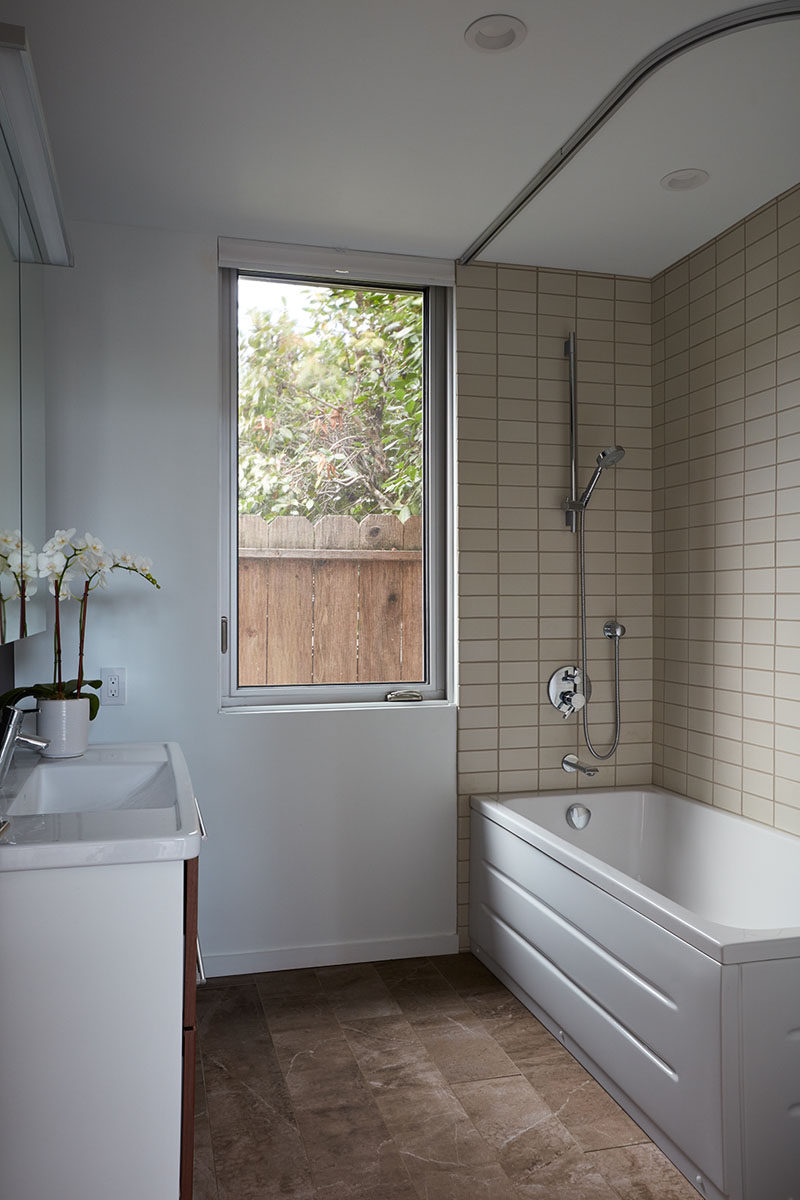 This simple bathroom has a tall window, and a large bath tub with shower is surrounded by cream colored rectangular tiles.