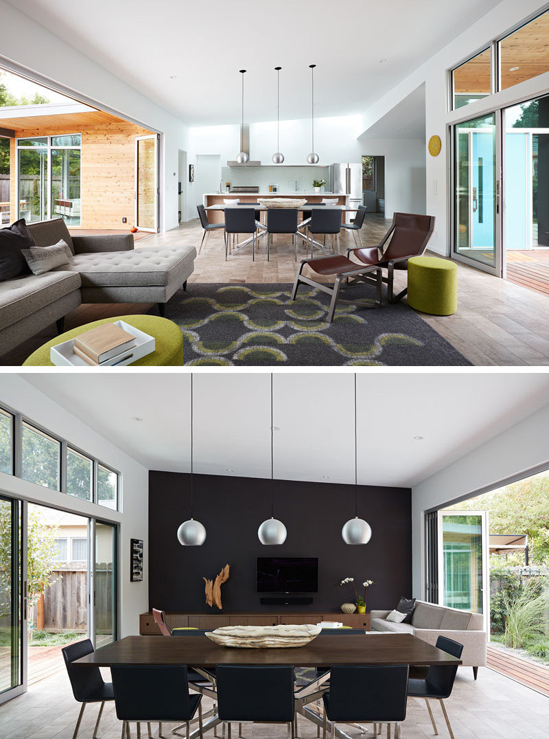 In this renovated house, the dining area separates the living room from the kitchen. Opposite the kitchen is the living room with a dark accent wall. Three silver, round, pendant lights hang above the wooden dining table, anchoring it in the large open room.