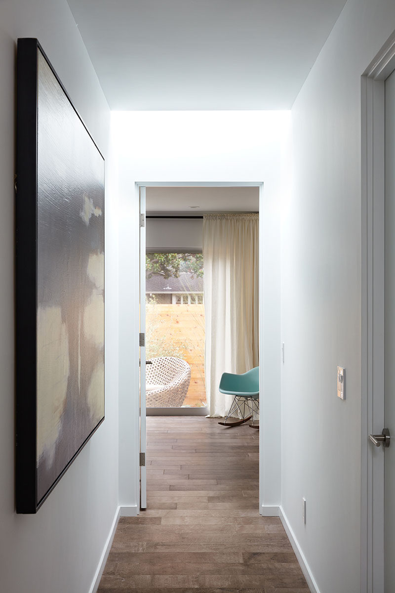 This white hallway has a skylight and leads to the bedrooms and bathrooms.
