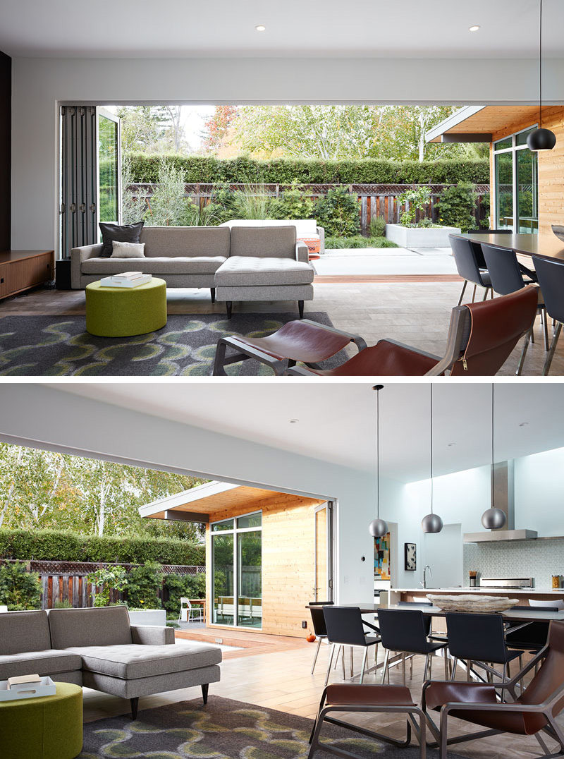 This modern open-plan living room looks out onto the patio through a wide, glass folding wall system. The gray, green, brown, and wood furniture match the colors of the outside space.