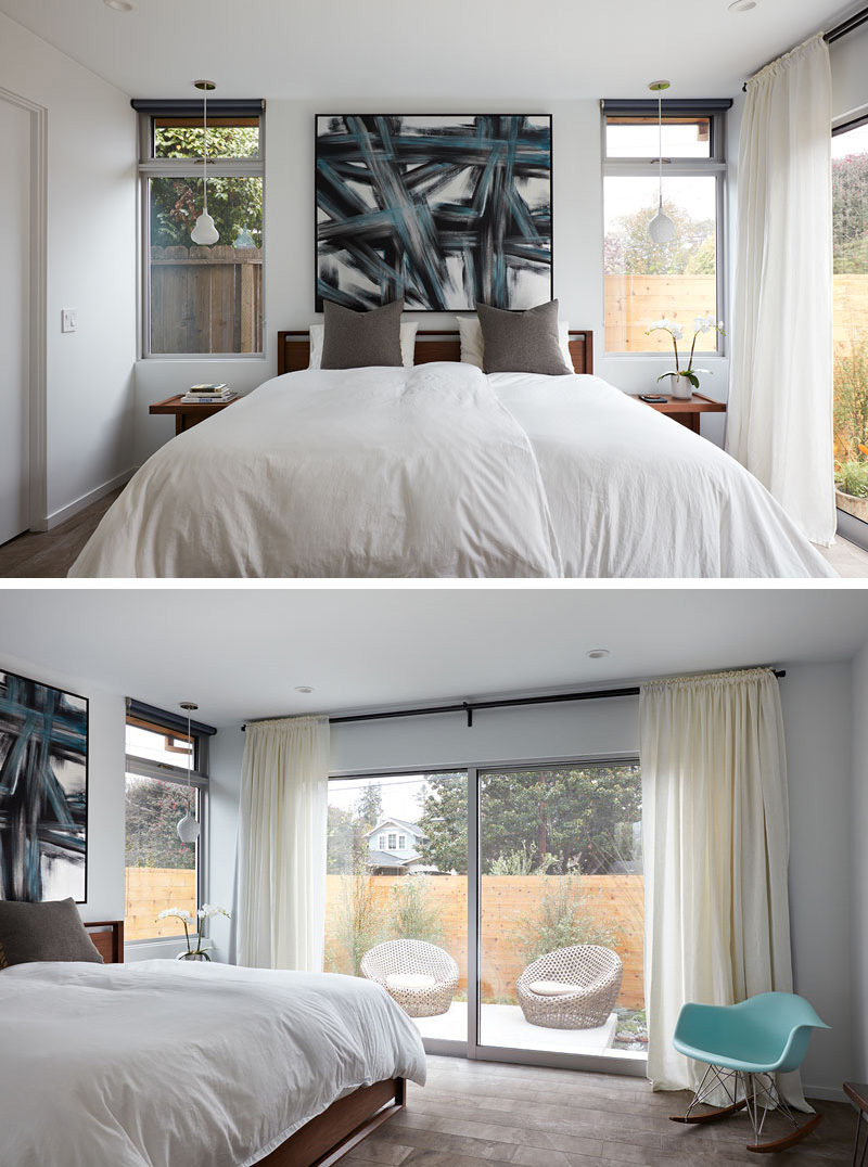 This master bedroom has a pop of color with a bold art piece that matches a blue Eames rocking chair in the corner of the room. The bed faces a large sliding glass door that looks out to a private patio.